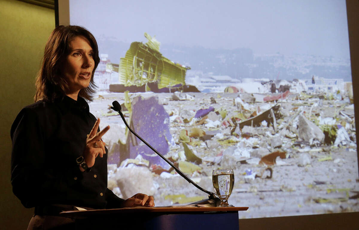 Deborah Hersman of the National Transportation Safety Board speaks in front of a photograph of the wreckage of Asiana Flight 214, which crashed on Saturday, July 6, 2013, at San Francisco International Airport, at a news conference in South San Francisco, Calif., Thursday, July 11, 2013. (AP Photo/Jeff Chiu)