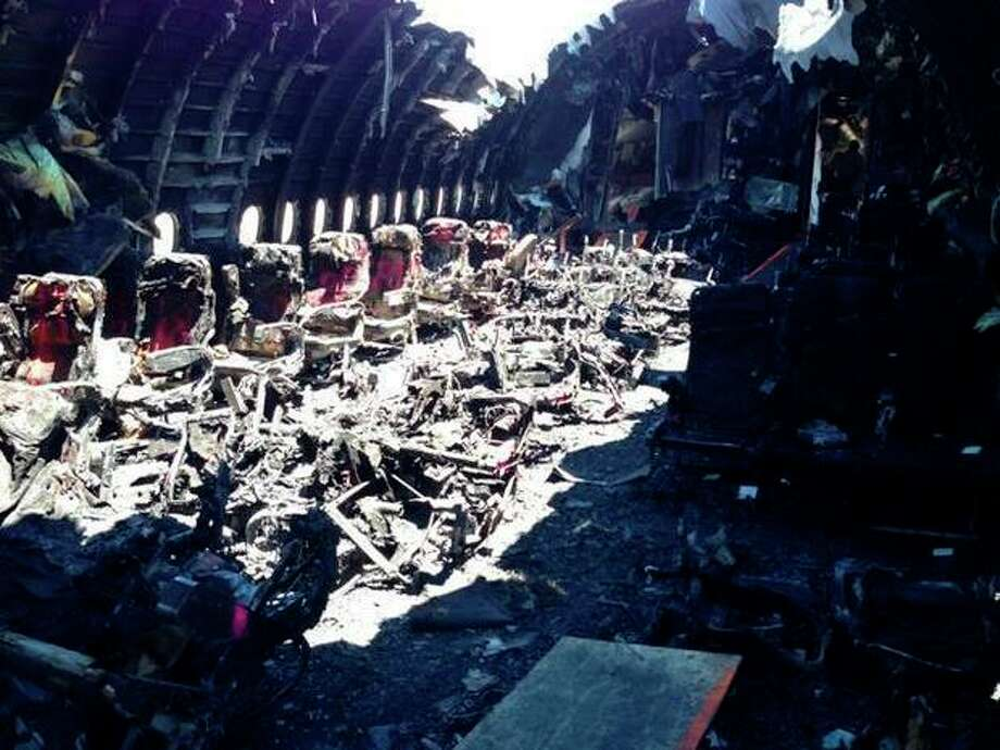This image released by the National Transportation Safety Board, on Thursday, July 11, 2013, shows the charred remains of Asiana Airlines Flight 214 in San Francisco. The Asiana flight crashed upon landing Saturday, July 6, at San Francisco International Airport, and two of the 307 passengers aboard were killed. (AP Photo/NTSB) / National Transportation Safety Board