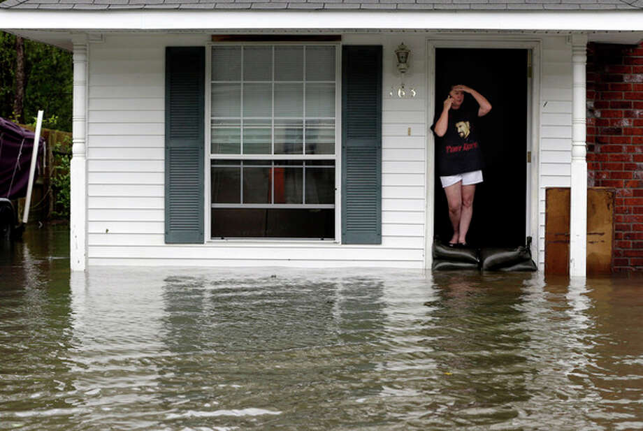 A resident whose home is surrounded by flood waters talks on the phone, Thursday, Aug. 30, 2012, in LaPlace, La. Isaac has caused major flooding in the region. (AP Photo/Eric Gay) / AP