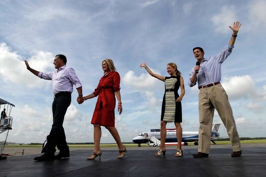 From left, Republican presidential nominee Mitt Romney, his wife Ann and his vice presidential running mate Rep. Paul Ryan, right, with his wife Janna, wave at supporters during a campaign event at Lakeland Linder Regional Airport, Friday, Aug. 31, 2012, Lakeland, Fla. (AP Photo/Mary Altaffer) / AP