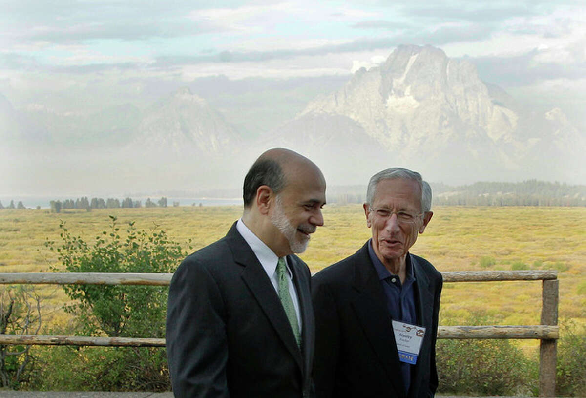 """With the Teton Mountains behind them, Federal Reserve Chairman Ben Bernanke, left, and Bank of Israel Governor Stanley Fischer walk together outside of the Jackson Hole Economic Symposium, Friday, Aug. 31, 2012, at Grand Teton National Park near Jackson Hole, Wyo. Bernanke made clear Friday that the Federal Reserve will do more to boost the economy because of high U.S. unemployment and an economic recovery that remains """"far from satisfactory."""" (AP Photo/Ted S. Warren)"""