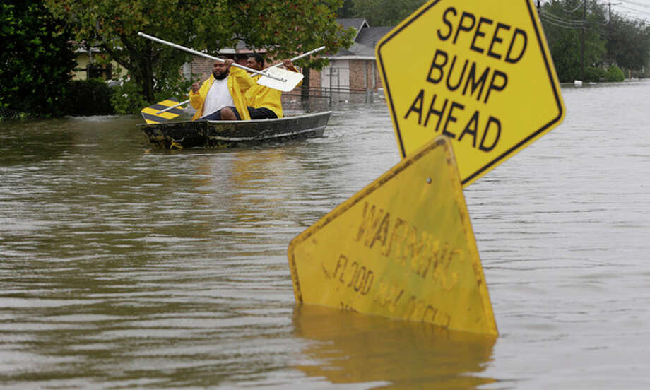 Isaac Fields, left, and Victor Jones use street signs to paddle a boat out of their flooded neighbor, Thursday, Aug. 30, 2012, in LaPlace, La. Isaac has caused major flooding in the region. (AP Photo/Eric Gay) / AP