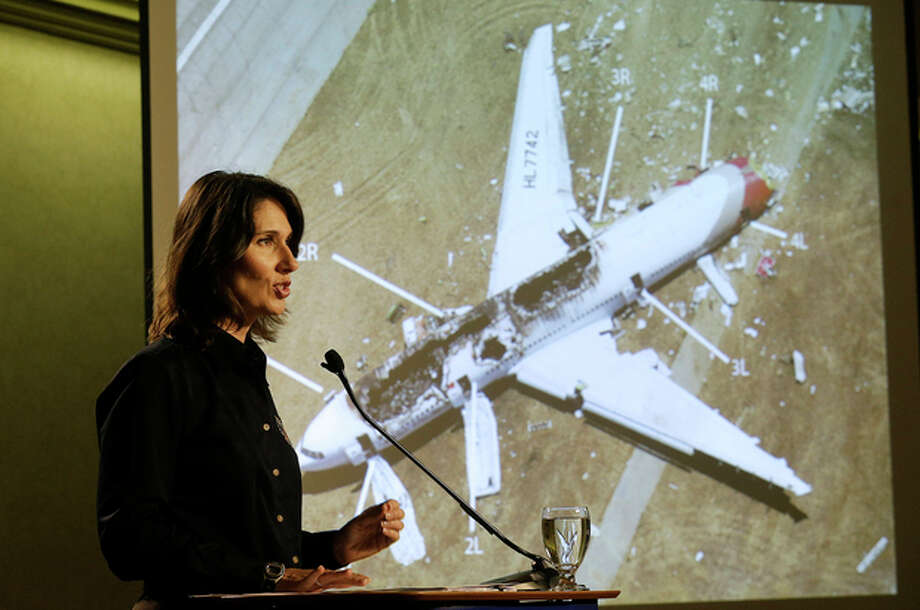 Deborah Hersman of the National Transportation Safety Board speaks in front of a photograph of Asiana Flight 214, which crashed on Saturday, July 6, 2013, at San Francisco International Airport, at a news conference in South San Francisco, Calif., Thursday, July 11, 2013. (AP Photo/Jeff Chiu) / AP