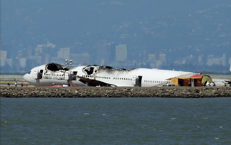 "The wreckage of Asiana Airlines Flight 214 that crashed upon landing Saturday at San Francisco International Airport sits on the tarmac Monday, July 8, 2013 in San Francisco. Investigators said the Boeing 777 was traveling ""significantly below"" the target speed during its approach and that the crew tried to abort the landing just before it smashed onto the runway on Saturday, July 6. Two of the 307 passengers aboard were killed. (AP Photo/Jeff Chiu) / AP"