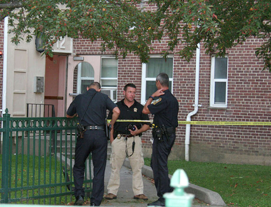 Hour photo/Chris BosakPolice discuss a shooting at Roodner Court Thursday evening in Norwalk.