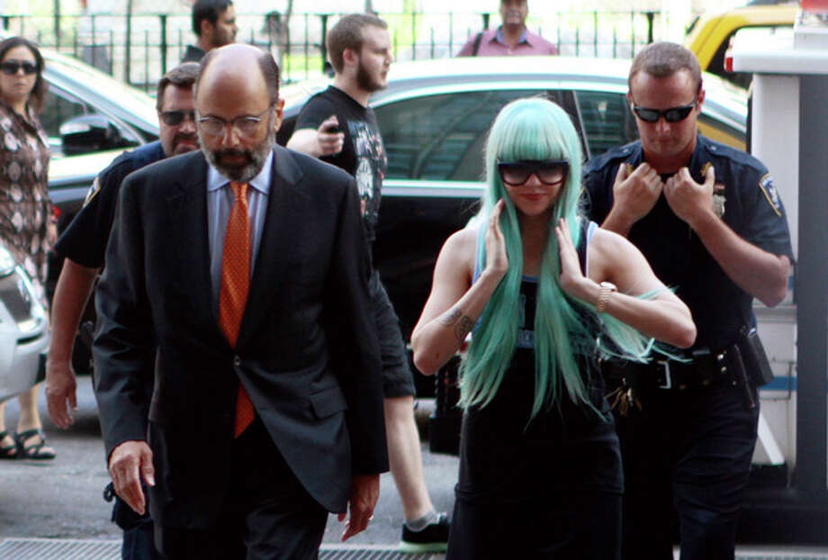 Amanda Bynes, accompanied by attorney Gerald Shargel, arrives for a court appearance in New York, Tuesday, July 9, 2013. The 27-year-old actress is charged with reckless endangerment and attempted tampering with physical evidence. Bynes was arrested in May after building officials called police to complain she was smoking pot in the lobby. Officers went to her apartment where they say they saw a bong sitting on the kitchen counter. Prosecutors say she tossed the bong out the window in front of the officers. (AP Photo/Bethan McKernan) / AP