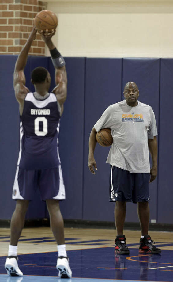 Charlotte Bobcats associate head coach Patrick Ewing, right, watches as Bismack Biyombo, left, shoots during a summer league basketball practice for the NBA team in Charlotte, N.C., Tuesday, July 9, 2013. (AP Photo/Chuck Burton)