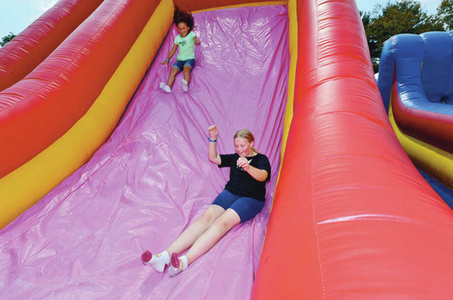 Anne Machata and Zoe Cohen use the inflatable slide at the Blues, Views and BBQ Festival in Westport Saturday.Hour photo / Erik Trautmann / (C)2012, The Hour Newspapers, all rights reserved