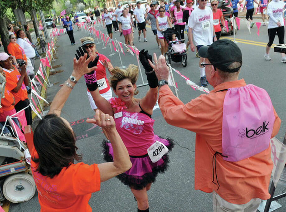 AP photoCancer survivor Julie Grimm high-fives Dr. Paula DeNitto and Dr. Ray Rudolph, right, after crossing the finish line for Saturday's Susan G. Komen Savannah Race for the Cure in Savannah, Ga. / Savannah Morning News