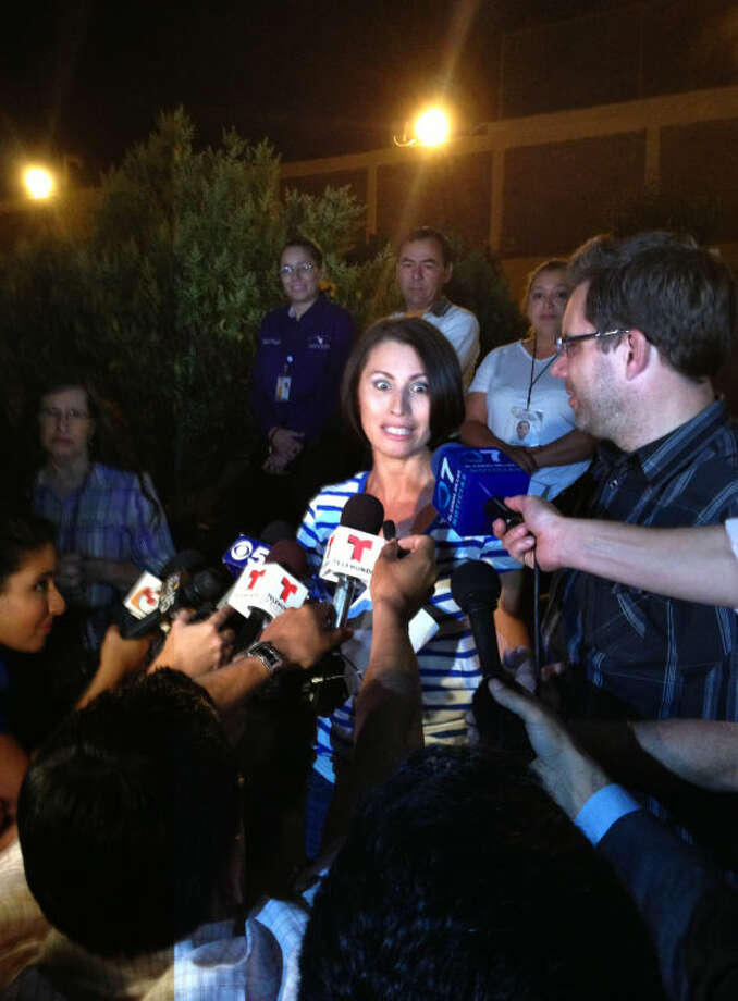 Yanira Maldonado, 42, center, accompanied by her husband, Gary, right, speaks to media after being released from a prison on the outskirts of Nogales, Mexico late Thursday, May 30, 2013. Maldonado, jailed in Mexico on a drug-smuggling charge, was released after court officials reviewed her case. She was arrested by the Mexican military last week after they found nearly 12 pounds (5.4 kilograms) of pot under her seat on the commercial bus traveling from Mexico to Arizona. (AP Photo/Cristina Silva)