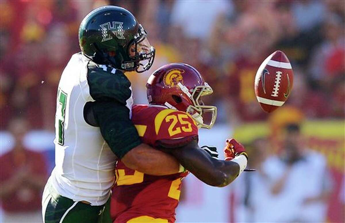 Hawaii linebacker Kamalani Alo, left, knocks the ball from the hands of Southern California running back Silas Redd during the first half of their NCAA college football game, Saturday, Sept. 1, 2012, in Los Angeles. The ball was recovered by Hawaii. (AP Photo/Mark J. Terrill)