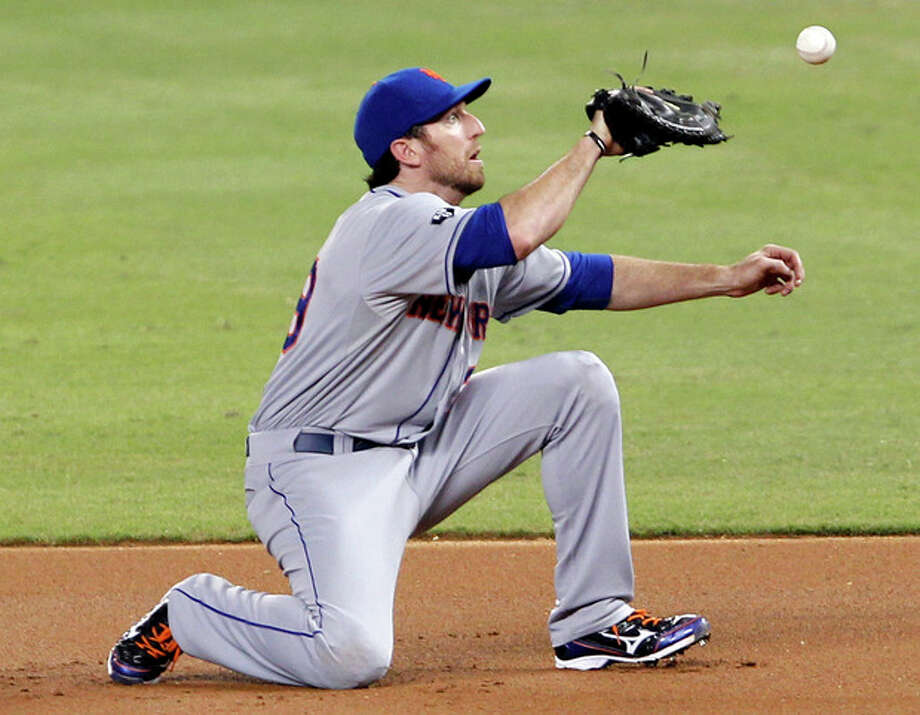 New York Mets first baseman Ike Davis is unable to hold on to a ground ball hit by Miami Marlins' Bryan Petersen in the first inning of a baseball game in Miami, Saturday, Sept. 1, 2012. Petersen was out at first base. (AP Photo/Alan Diaz) / AP