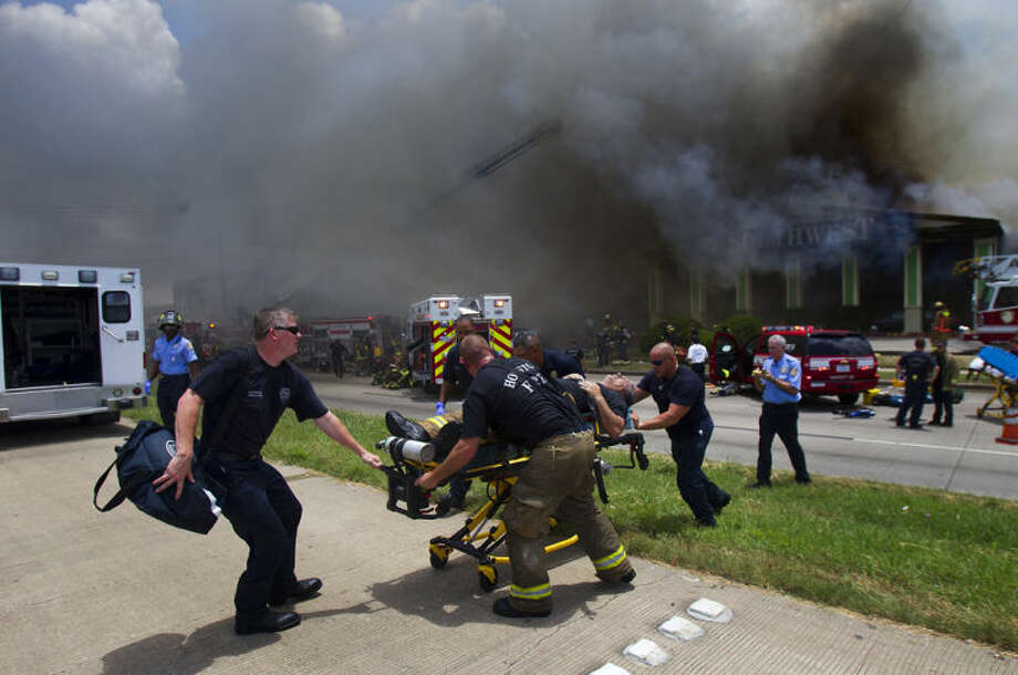 A firefighter is wheeled to an ambulance after fighting a fire at the Southwest Inn, Friday, May 31, 2013, in Houston. A fire that engulfed a Houston motel has injured at least six firefighters, including two critically, and three people are missing. (AP Photo/Houston Chronicle, Cody Duty) MANDATORY CREDIT