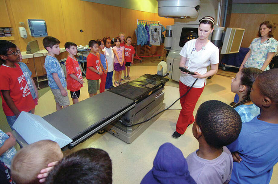 Hour Photo/Alex von Kleydorff Radiation Therapist Ashley Hamel starts to rotate the Linear Accelerator for 2nd graders from Wolfpit School. The group raises money by reading and donates it to The Whittinghan Cancer Center at Norwalk Hospital / 2013 The Hour Newspapers