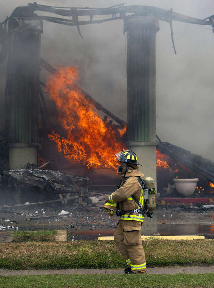 A firefighter stands near a fire at the Southwest Inn, Friday, May 31, 2013, in Houston. A fire that engulfed a Houston motel has injured at least six firefighters, including two critically, and three people are missing. (AP Photo/Houston Chronicle, Cody Duty) MANDATORY CREDIT