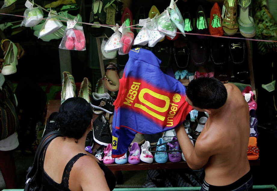 A shopper looks at a copy of a FC Barcelona soccer team shirt with the name of player Lionel Messi at an outdoor market where the government allows licensed vendors to sell their goods in downtown Havana, Cuba, Friday, Aug. 31, 2012. A jump in import taxes on Monday, Sept. 3 threatens to make life tougher for some of Cuba's new entrepreneurs who the government has been trying to encourage as it cuts a bloated workforce in the socialist economy. In Cuba, the average monthly wage is about $20. (AP Photo/Franklin Reyes) / AP