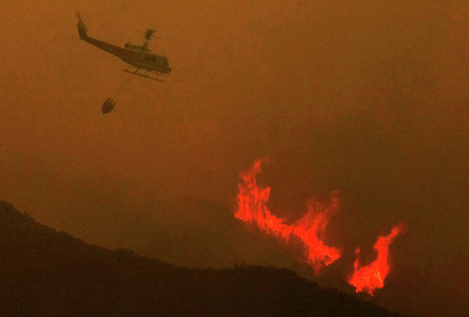 A helicopter prepares to drop a load of water on the Power House fire that has burned hundreds of acres in Green Valley, Calif. on Thursday, May 30, 2013. The wildfire in the mountains north of Los Angeles has been slowed by morning overcast but authorities say about 25 homes have been evacuated as scattered flames continue to leap hillsides. Authorities Friday morning ordered homes evacuated on San Francisquito Canyon Road in the Angeles National Forest north of Castaic. (AP Photo/Los Angeles Times, Genaro Molina) NO FORNS; NO SALES; MAGS OUT; ORANGE COUNTY REGISTER OUT; LOS ANGELES DAILY NEWS OUT; VENTURA COUNTY STAR OUT; INLAND VALLEY DAILY BULLETIN OUT; MANDATORY CREDIT, TV OUT / Los Angeles Times