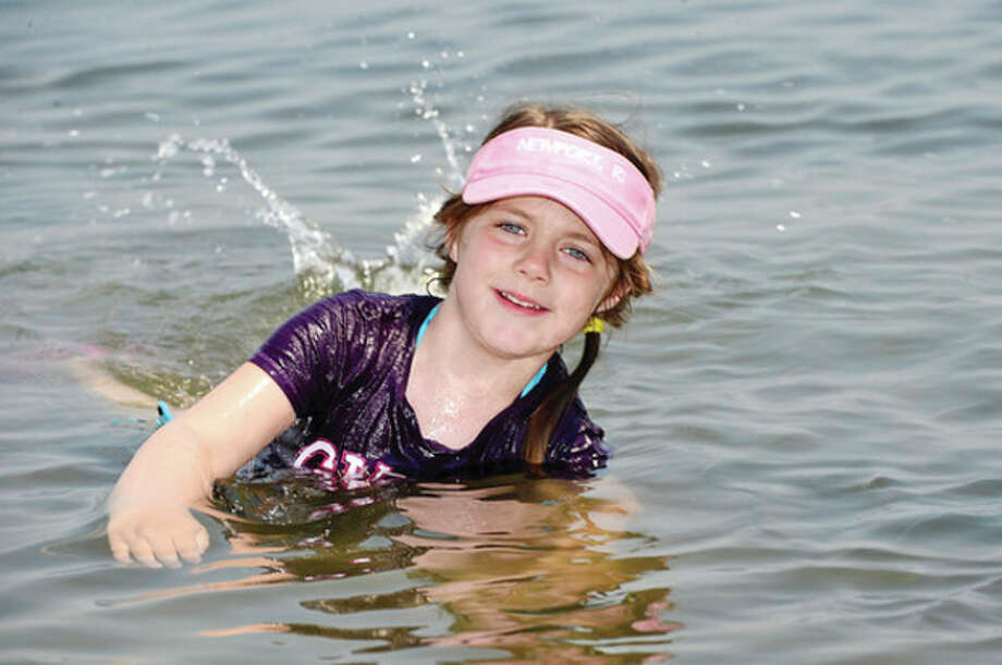Chloe Ballard, 4, beats the heat at Calf Pasture Beach Thursday by dipping in Long Island Sound.Hour photo / Erik Trautmann / (C)2013, The Hour Newspapers, all rights reserved
