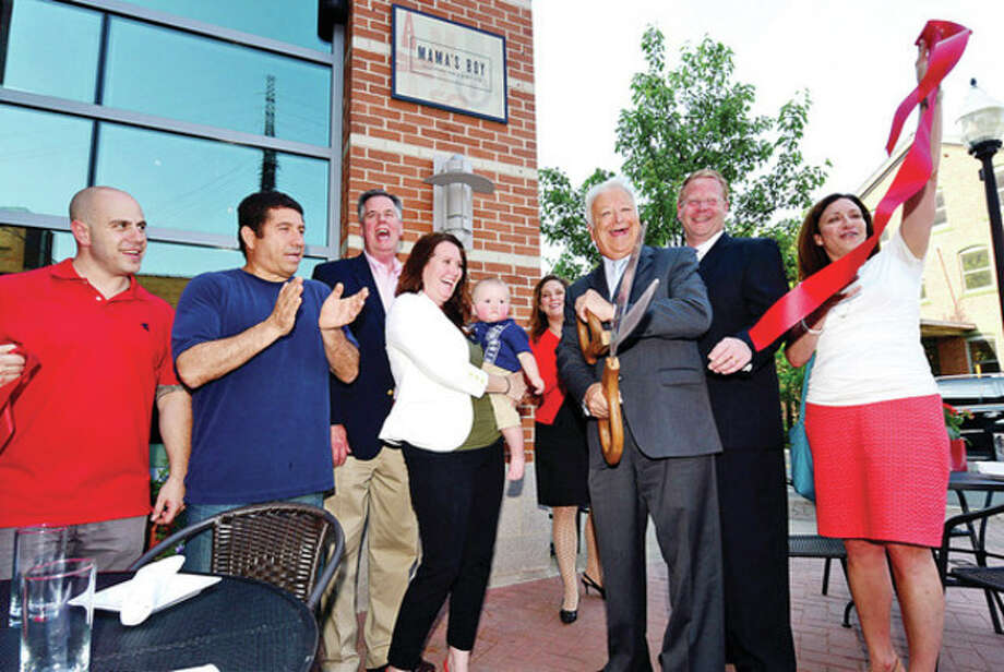 John Lunghi and Amiel Dorel of Mama's Boy, Greater Norwalk Chamber of Commerece president Ed Musante, Mama's Boy owner Greer Frederick's with her son, Jax, Stacey Hascoe, assistant director of the SONO Corporate, Norwalk Mayor Richard Moccia, Councilman David McCarthy and Norwalk Parking Authority Director Kathryn Hebert, cut the ribbon for the new Mama's Boy restaurant on North Water Street Thursday.Center Hour photo / Erik Trautmann / (C)2013, The Hour Newspapers, all rights reserved