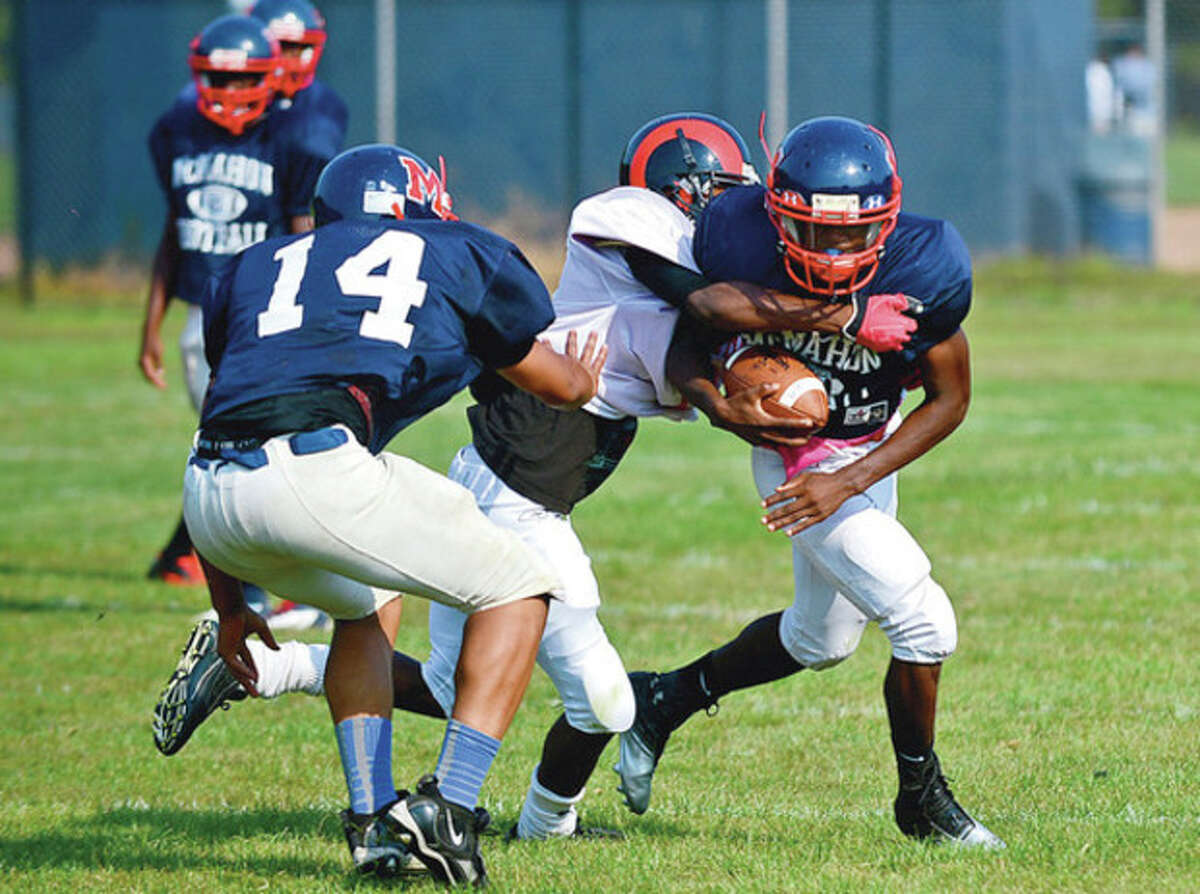 Hour photo/Erik Trautmann Brien McMahon's Travon Forney tries to escape the grasp of a Bridgeport Central defender during Saturday's Wilton High preseason football jamboree. Nine teams took part in the jamboree, which included play at the varsity and JV levels.