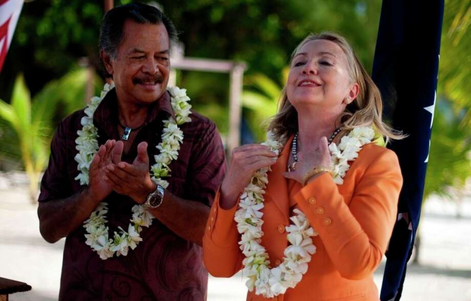 U.S. Secretary of State Hillary Rodham Clinton adjusts her black pearl necklace, a gift from Cook Island Prime Minister Henry Puna, left, during an event on sustainable development and conservation, in Rarotonga, Cook Islands, Friday, Aug. 31, 2012. (AP Photo/Jim Watson, Pool) / POOL AFP