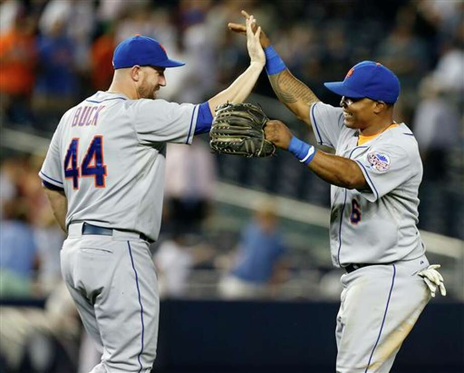 CORRECTS BUCK'S POSITION - New York Mets right fielder Marlon Byrd, right, celebrates with designated-hitter John Buck (44) after the the Mets defeated the New York Yankees 3-1 to complete a four game sweep after an interleague baseball game series at Yankee Stadium in New York, Thursday, May 30, 2013. (AP Photo/Kathy Willens) / AP