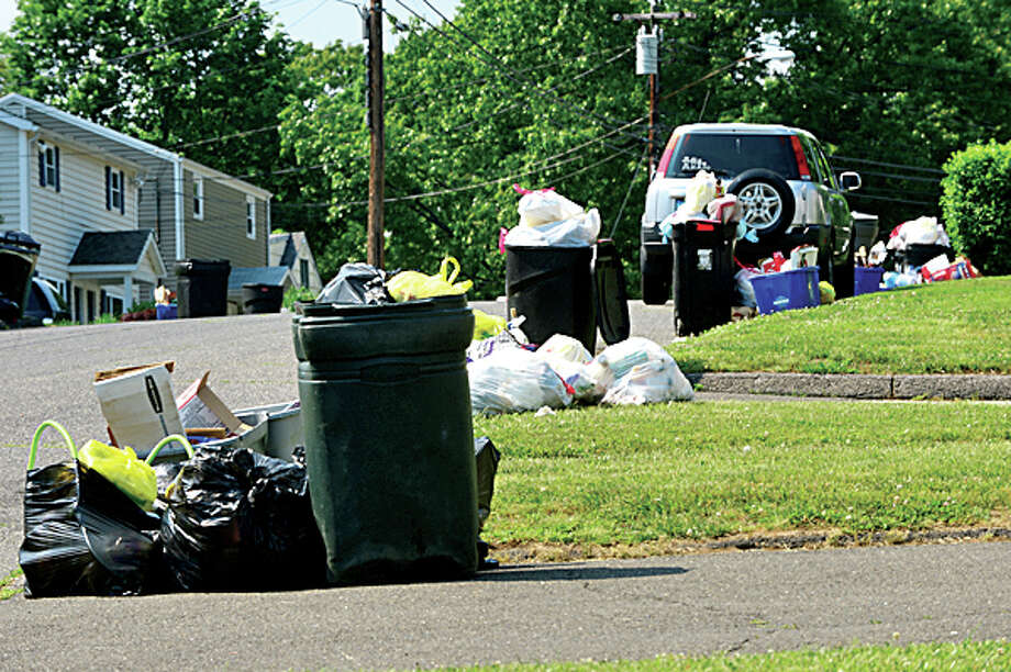 Trash lines the curb on Ferris Ave after trash that was due for pick up Tuesday was still out Thursday afternoon. Hour photo / Erik Trautmann / (C)2013, The Hour Newspapers, all rights reserved