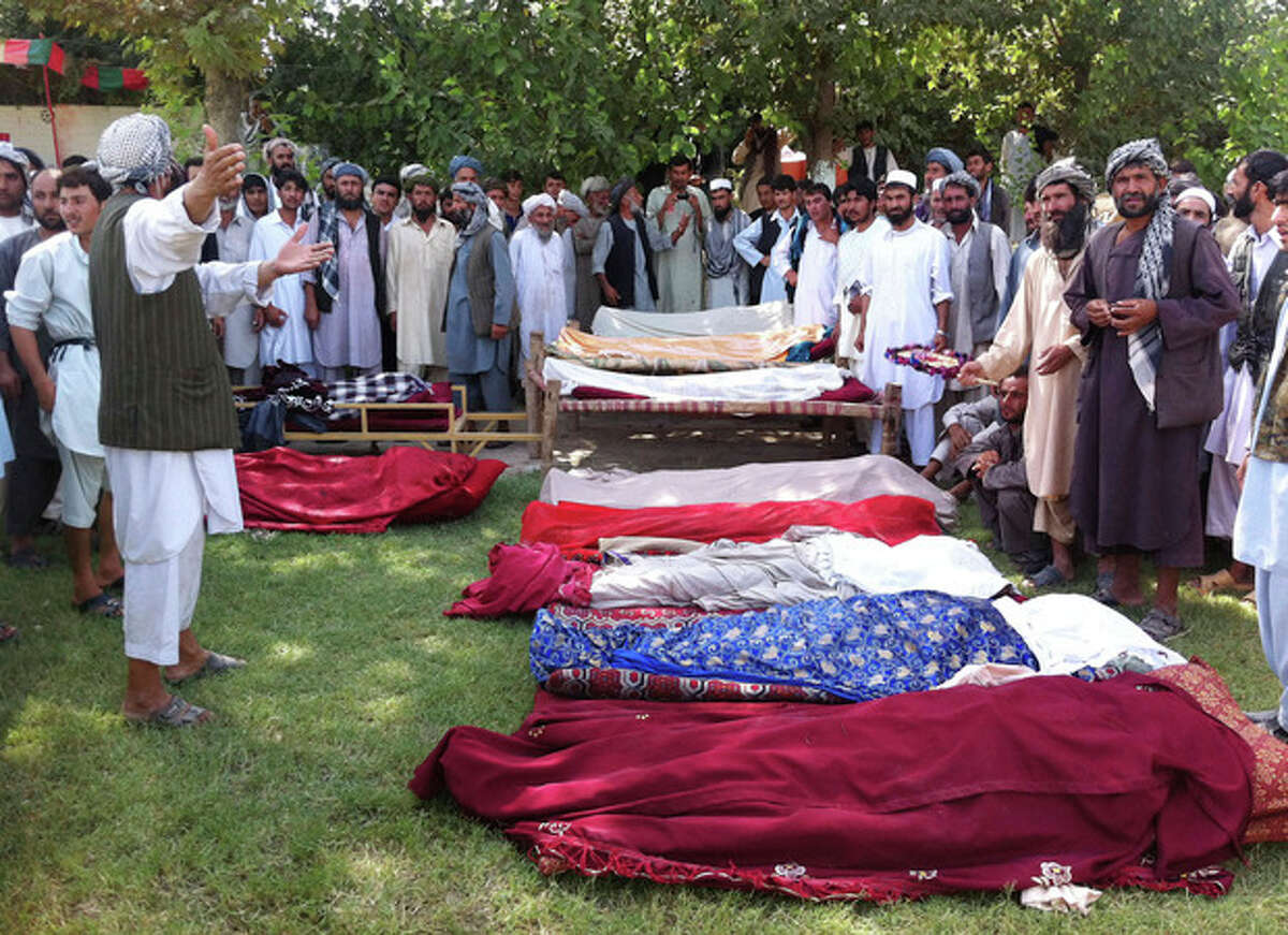 The covered bodies of Afghans who were killed during an apparent clash between tribal leaders lie on the ground in Kunduz, north of Kabul, Afghanistan, Sunday, Sept. 2, 2012. The violence that left at least ten dead, broke out Sunday when gunmen from one village killed the brother-in-law of a tribal leader in another, said Sarwar Husseini, spokesman for the provincial police chief. (AP Photo/Fulad Hamdard)