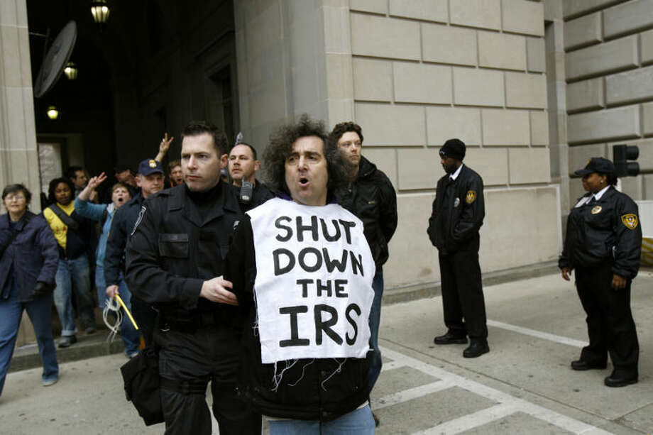 FILE - This March 19, 2008 file photo shows an Iraq War demonstrator gets arrested outside the Internal Revenue Service (IRS) in Washington during a protest on the fifth anniversary of the war in Iraq. For a time, the Internal Revenue Service inspired awe and admiration in Americans, not just trepidation and lame jokes about death and taxes. Everyone loved the revenue agents when they put away Al Capone, the Chicago underworldÕs master of brutality and bribes, in a coup so spectacular it scared other gangsters straight. But that sentiment is of ages past. (AP Photo/Jose Luis Magana, File)