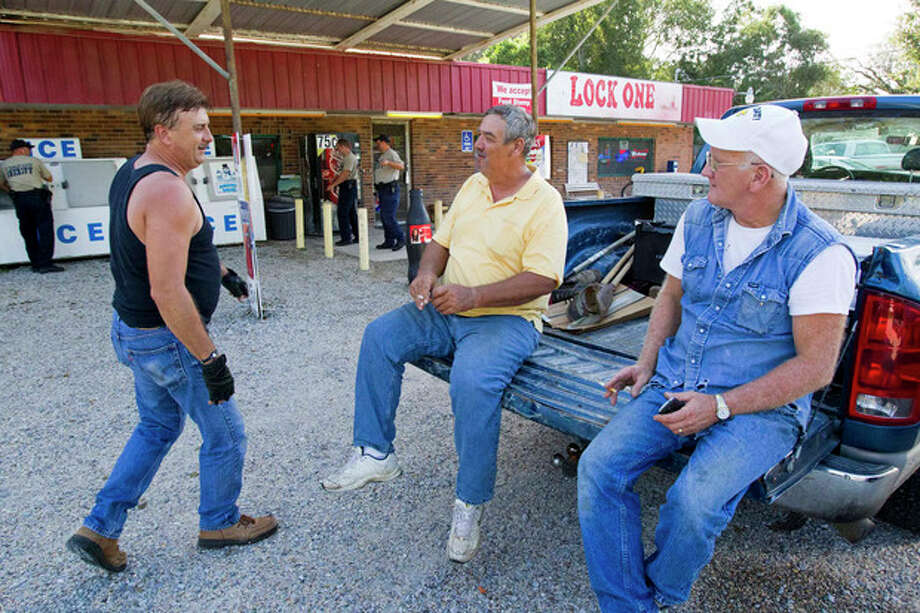 Buddy Davis, left, James Moorman and Carl Crawford shoot the breeze at the Lock One Pantry north of Pearl River after an evacuation was ordered after Lock 2 became in danger of failing Saturday, September 1, 2012, on the Pearl River navigational canal in St. Tammy Parish, La.. (AP Photo/The Times-Picayune, Scott Threlkeld) MAGS OUT; NO SALES; USA TODAY OUT / THE TIMES-PICAYUNE