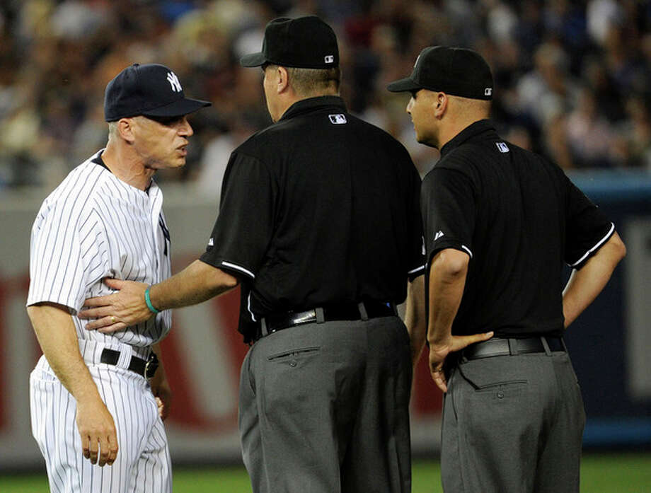 New York Yankees manager Joe Girardi, left, is restrained by first base umpire Gary Cederstrom after Girardi was ejected by second base umpire Vic Carapazza, right, during the fifth inning of a baseball game against the Boston Red Sox, Friday, May 31, 2013, at Yankee Stadium in New York. (AP Photo/Bill Kostroun) / FR51951 AP
