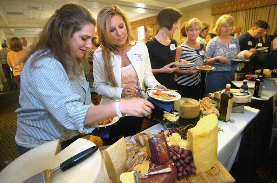 Hour Photo/Alex von Kleydorff. Stacey Hascoe and Eleni Sotiriou sample some of the Italian specialty cheeses at the buffet by Bulls Head Market