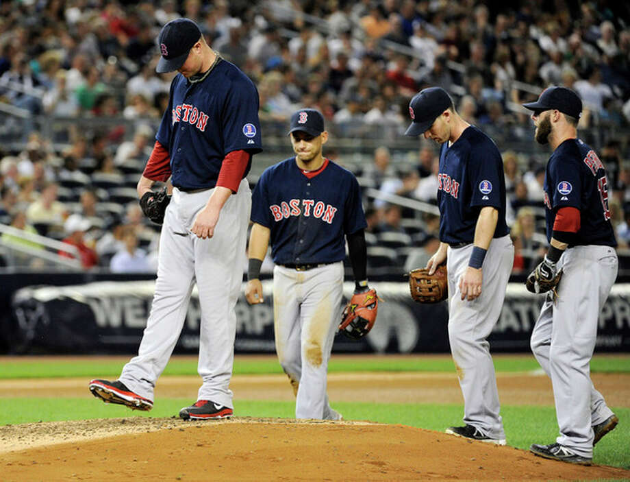 Boston Red Sox pitcher Jon Lester, left, reacts as his manager comes out to take him out during the seventh inning of a baseball game against the New York Yankees, Friday, May 31, 2013, at Yankee Stadium in New York. (AP Photo/Bill Kostroun) / FR51951 AP