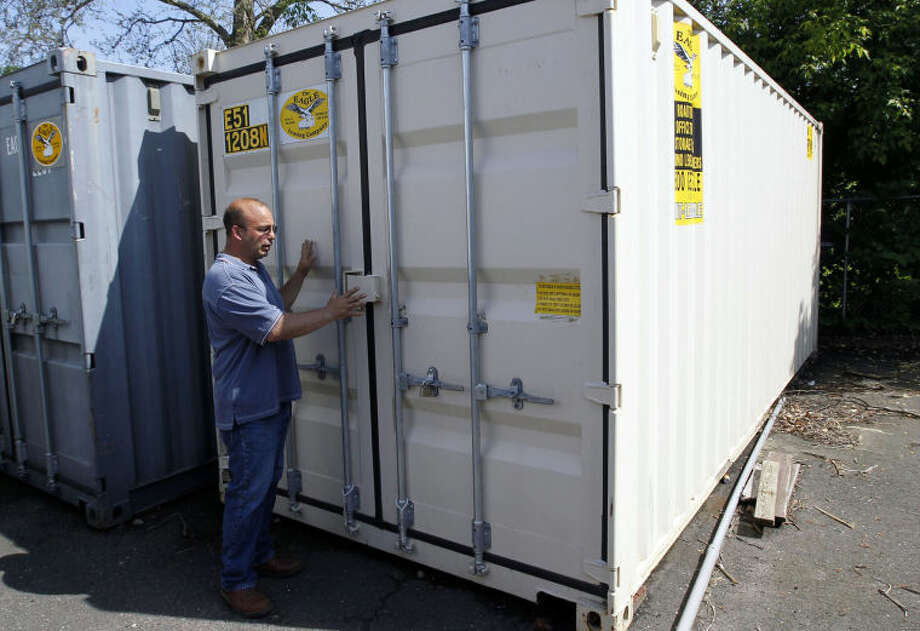 ADVANCE FOR WEEKEND EDITIONS JUNE 1-2 - In this May 20, 2013 photo, Joseph Palmieri, President of Connecticut Tank Removal Inc. and CEO of Palmieri Farm, opens a storage container, which he hopes will be transformed into a growing chamber for medical marijuana, in Bridgeport, Conn., Palmieri expects to house the container inside a building he purchased. (AP Photo/The Republican-American, Christopher Massa)