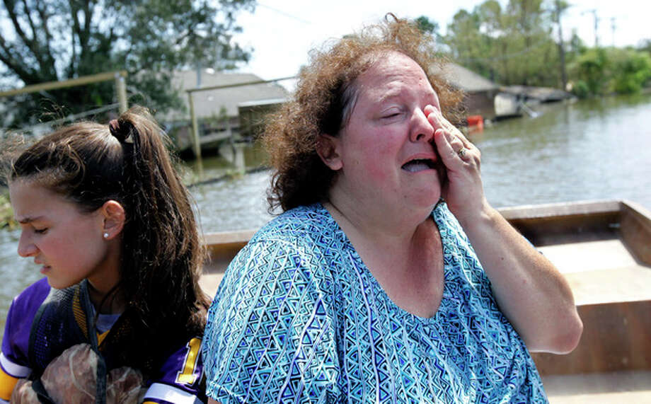 Angela Serpas cries as she sees her flooded home for the first time since Hurricane Isaac pushed a 10-foot storm surge into Braithwaite, La., Saturday, Sept. 1, 2012. At right is her daughter Lainy Serpas, 11. While New Orleans streets were bustling again and workers were returning to offshore oil rigs, thousands of evacuees couldn't return home to flooded low-lying areas of Louisiana and more than 400,000 sweltering electricity customers in the state remained without power. (AP Photo/Gerald Herbert) / AP