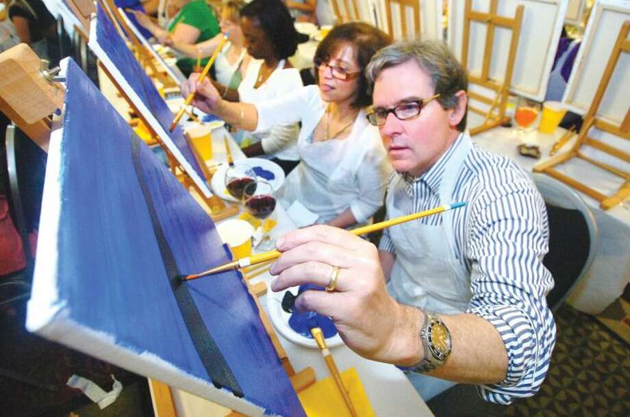 Hour Photo/Alex von Kleydorff. Kathy and Dan McCrory work on their canvas of Starry Night at Arts and Carafes at The Hilton Garden Inn.