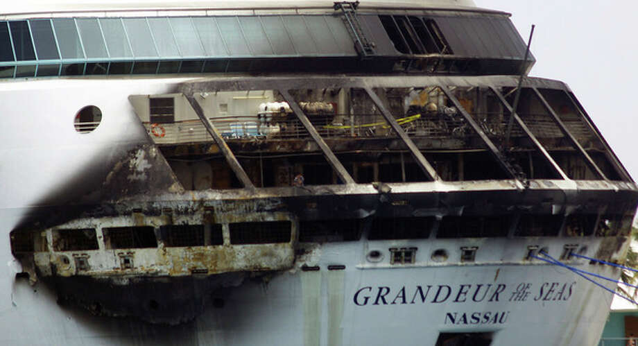 The fire-damaged exterior of Royal Caribbean's Grandeur of the Seas cruise ship is seen while docked in Freeport, Grand Bahama island, Monday, May 27, 2013. Royal Caribbean said the fire occurred early Monday while on route from Baltimore to the Bahamas on the mooring area of deck 3 and was quickly extinguished. All 2,224 guests and 796 crew were safe and accounted for. (AP Photo/The Freeport News, Jenneva Russell) / The Freeport News