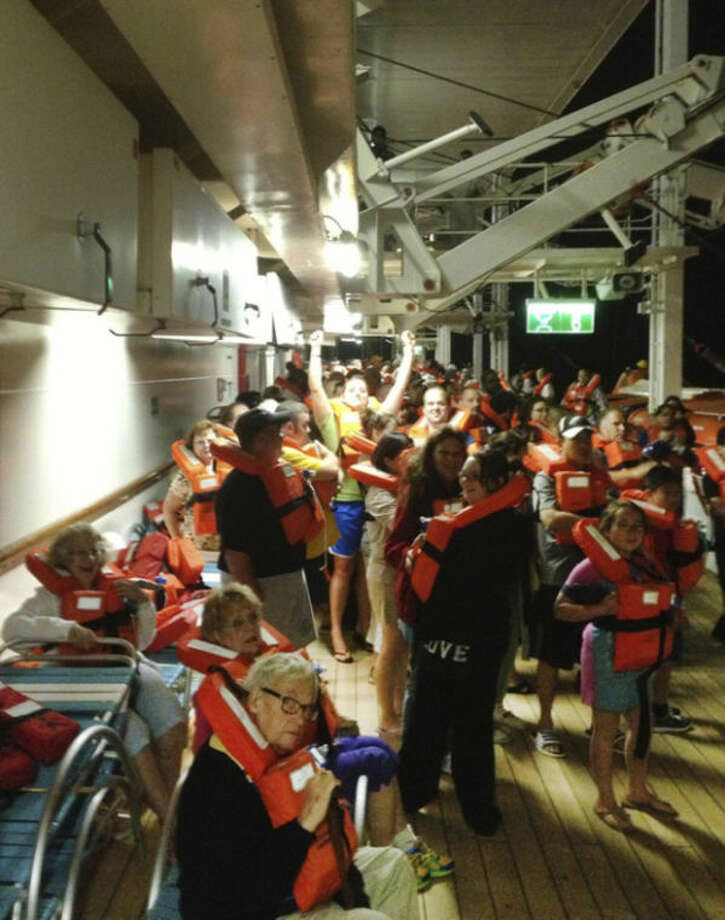 In this Monday, May 27, 2013 photo provided by passenger Marc Bell, passengers aboard the Royal Caribbean's Grandeur of the Seas cruise ship muster after a fire broke out during the ship's voyage from Baltimore to the Bahamas. Royal Caribbean said the fire occurred early Monday and was extinguished after about two hours with no injuries reported. (AP Photo/Marc Bell)