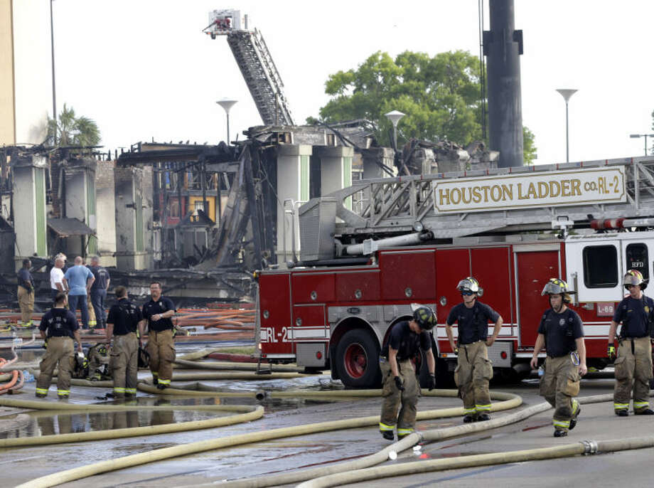 Houston firefighters clean up the scene where four firefighters were killed while battling a fire that engulfed a motel and restaurant on Friday, May 31, 2013, in Houston. At least five other people were hospitalized, authorities said. (AP Photo/David J. Phillip))