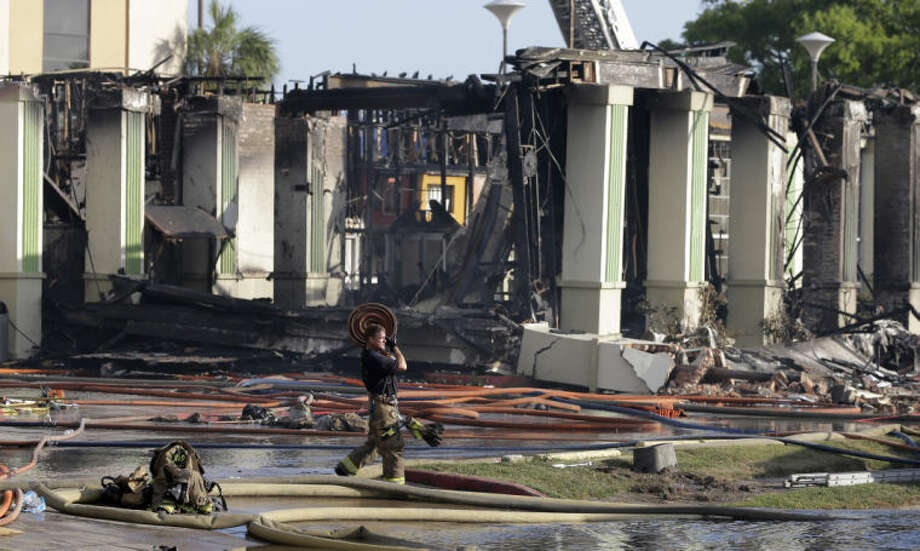 A Houston firefighter carries a firehose from the scene where four firefighters were killed while battling a fire that engulfed a motel and restaurant on Friday, May 31, 2013, in Houston. At least five other people were hospitalized, authorities said. (AP Photo/David J. Phillip)