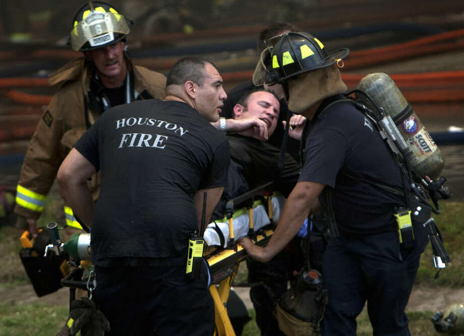 A firefighter is wheeled to an ambulance after fighting a fire at the Southwest Inn, Friday, May 31, 2013, in Houston. Four firefighters have died and at least five people have been hospitalized. (AP Photo/Houston Chronicle, Cody Duty)