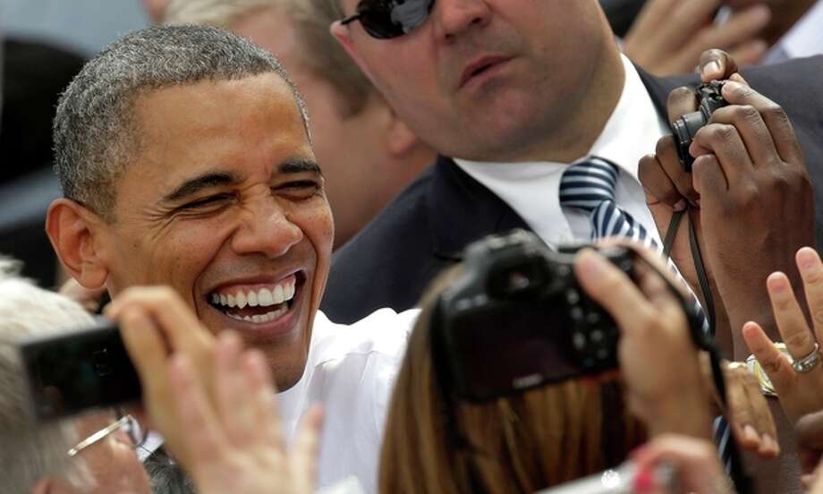 President Barack Obama greets the crowd during a campaign stop at the Living History Farms Saturday, Sept. 1, 2012, in Des Moines, Iowa. (AP Photo/Charlie Riedel) / AP
