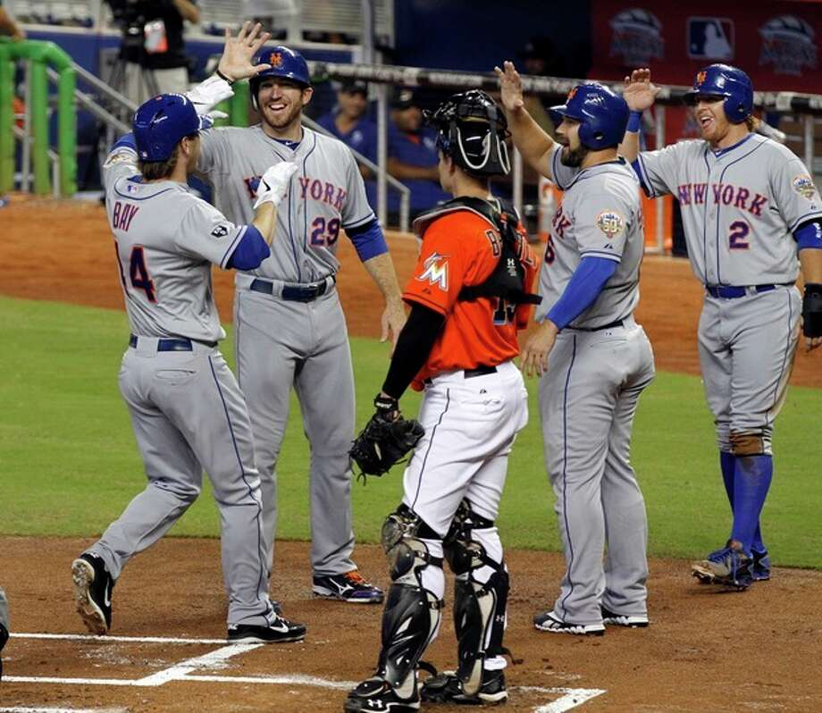 New York Mets' Jason Bay (44) is congratulated by teammates Ike Davis (29), Kelly Shoppach (6) and Justin Turner (2) after hitting a grand slam against the Miami Marlins as Marlins catcher Rob Brantly (19) watches the celebration in the first inning of a baseball game in Miami, Sunday, Sept. 2, 2012. (AP Photo/Alan Diaz) / AP
