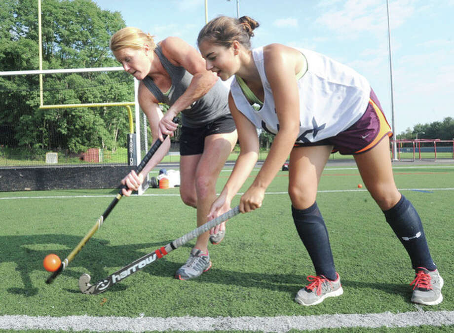 Hour photo/Matthew VinciFormer U.S. Olympic field hockey team standout Carrie Lingo, left, works with Annie Cornbrooks at the field hockey clinic Sunday for Wilton girls at Memorial Stadium in Wilton.