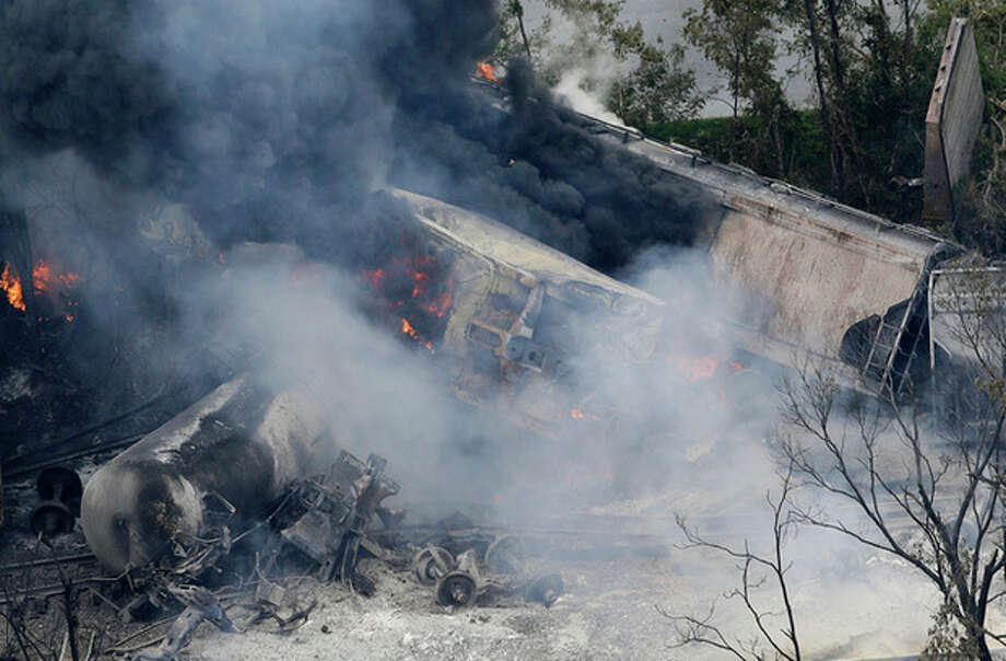 A fire burns at the site of a CSX freight train derailment, Tuesday, May 28, 2013, in Rosedale, Md., where fire officials say the train crashed into a trash truck, causing an explosion that rattled homes at least a half-mile away and collapsed nearby buildings, setting them on fire. (AP Photo/Patrick Semansky) / AP