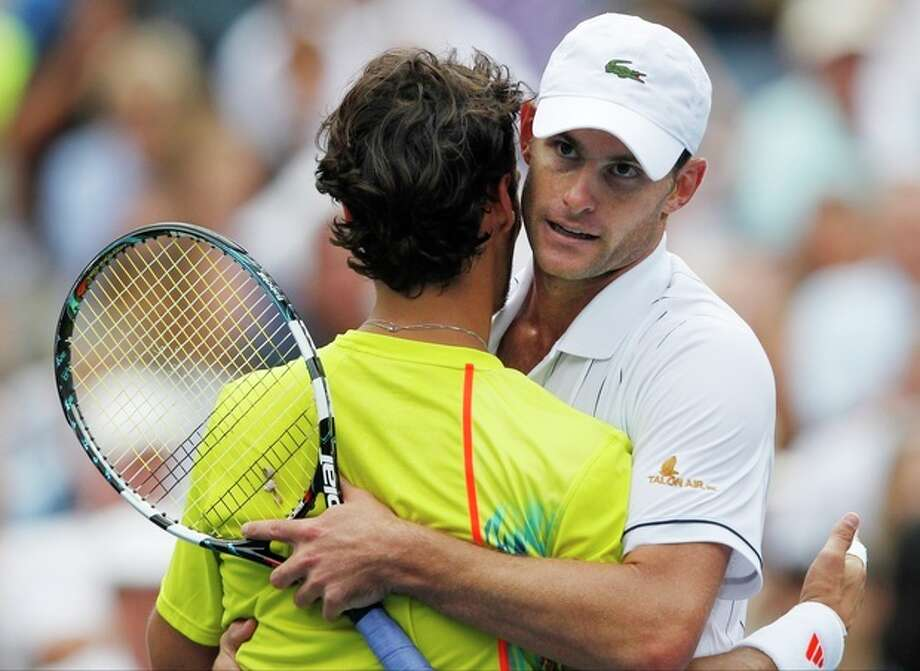 Andy Roddick hugs Italy's Fabio Fognini after their match in the third round of play at the 2012 US Open tennis tournament, Sunday, Sept. 2, 2012, in New York. Roddick won the match. (AP Photo/Mel C. Evans) / AP