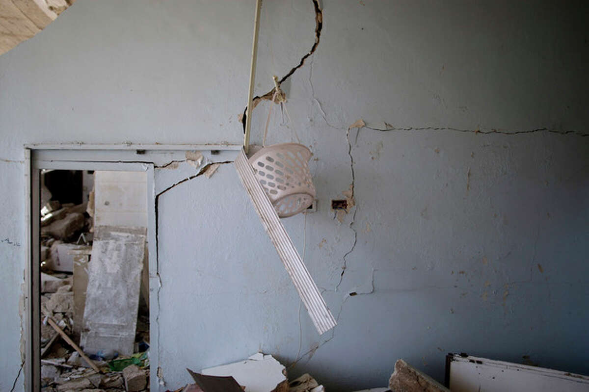 In this Wednesday, Aug. 29, 2012 photo, a plastic bucket hangs on a damaged wall of a Syrian house, one of more than a dozen homes destroyed in a Syrian government airstrike on August 15, 2012, that killed more than 40 people in Azaz, on the outskirts of Aleppo, Syria. Over the past week, survivors and relatives have returned daily to collect from the rubble what can be salvaged as they also relive the day of the airstrike. (AP Photo/Muhammed Muheisen)