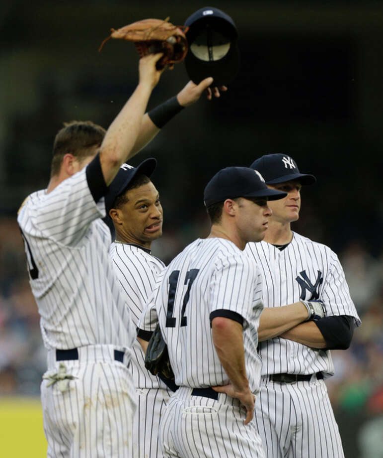 New York Yankees second baseman Robinson Cano, second from left, and teammates react after starting pitcher David Phelps allowed five runs in the first inning of an interleague baseball game against the New York Mets at Yankee Stadium in New York, Wednesday, May 29, 2013. Yankees shortstop Reid Brignac, left, third baseman Jayson Nix (17) and first baseman Lyle Overbay look on. (AP Photo/Kathy Willens) / AP