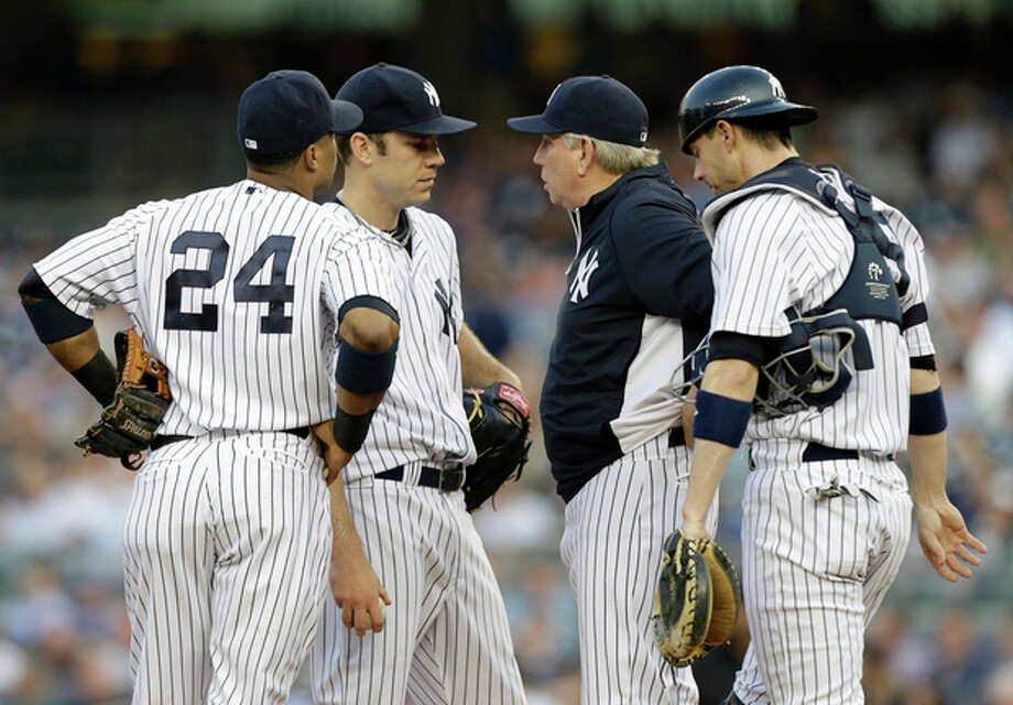 New York Yankees pitching coach Larry Rothschild, second from right, talks to starting pitcher David Phelps as second baseman Robinson Cano (24) and catcher Chris Stewart (19) listen in during the first inning of an interleague baseball game against the New York Mets at Yankee Stadium in New York, Wednesday, May 29, 2013. Phelps allowed five runs and only recorded one out before manager Joe Girardi removed him from the game. (AP Photo/Kathy Willens) / AP