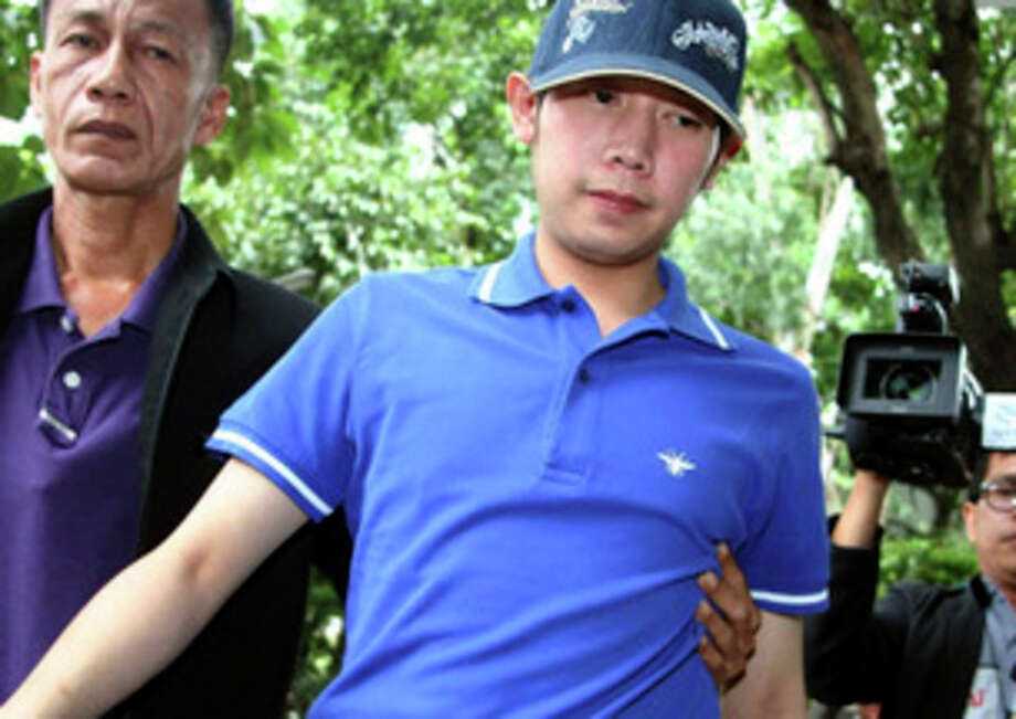 Vorayuth Yoovidhya, a grandson of late Red Bull founder Chaleo Yoovidhaya, is taken by a plain-clothes police officer for investigation Monday, Sept. 3, 2012 in Bangkok, Thailand. Vorayuth, believed to be in his late 20s, is suspected of driving a Ferrari that struck and killed a policeman and then dragged the officer's body down a Bangkok street in an early-morning, hit-and-run accident, police said Monday. (AP Photo) THAILAND OUT / AP